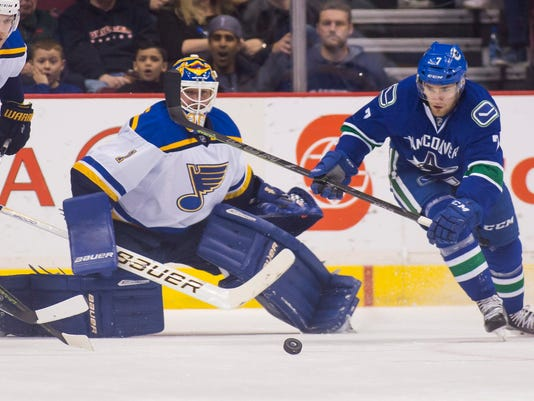 Vancouver Canucks' Linden Vey (7) skates for the puck near St. Louis Blues' goalie Brian Elliott (1) during first period NHL hockey action in Vancouver, British Columbia, Saturday, March 19, 2016. (Ben Nelms/The Canadian Press via AP)