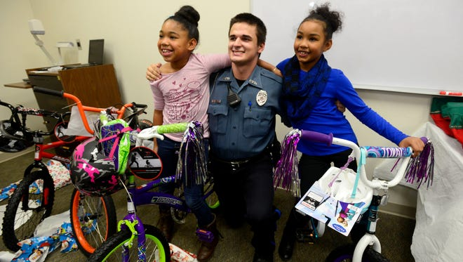 Cadet Reggie Allen has his photo taken with sisters Nickayla, left, and Addyson Cook on Monday during the Pensacola Police Department's annual childrens' Christmas party. Selected families and children in need were invited to have an early Christmas with officers and receive gifts through a $5,000 grant provided by the Kugleman Foundation.