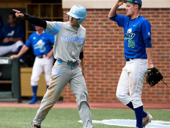 North Carolina's Brandon Riley, left, points toward