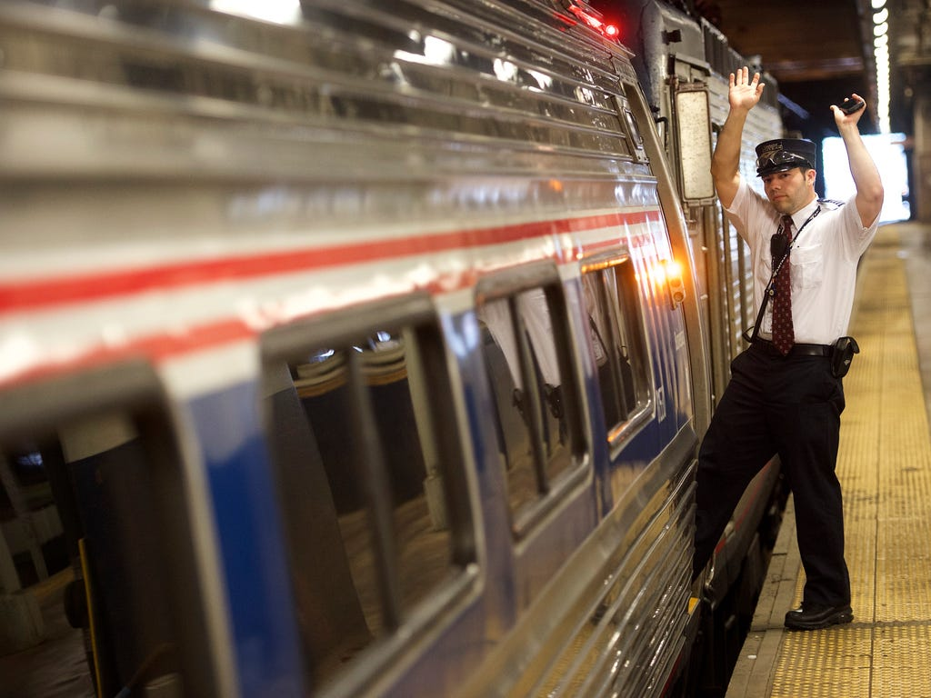 A conductor signals to a fellow conductor before departure as Amtrak resumes northbound service from 30th Street Station with a 5:53 a.m. train, after last week's derailment in Philadelphia.
