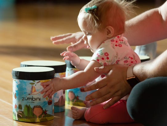 Mackenzie Miller, 7-months-old, plays with the drums during a Zumbini class.