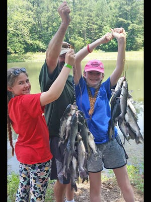 Laura Kennedy (left) and her sister Leah Kennedy display their catch of the day with a little help from their dad Les Hughes. The girls participated in Fairview's Annual Fishing Rodeo on June 9 at Evergreen Lake.