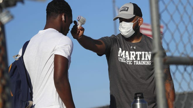 Before entering the field gates for football strength and conditioning camp at Arlington Martin High School, athletic trainer Joey Pena, right, uses a thermometer on the forehead of sophomore running back Gervawn Neville for a temperature check last Thursday in Arlington, Texas. While states have been easing the economic and social lockdowns prompted by the coronavirus pandemic, some are now letting high school athletes return for summer workouts before teachers have even figured out how they are going to hold classroom instruction.