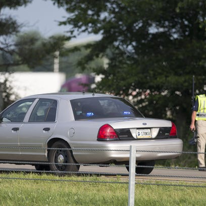 An investigator at the scene of an earlier fatal crash