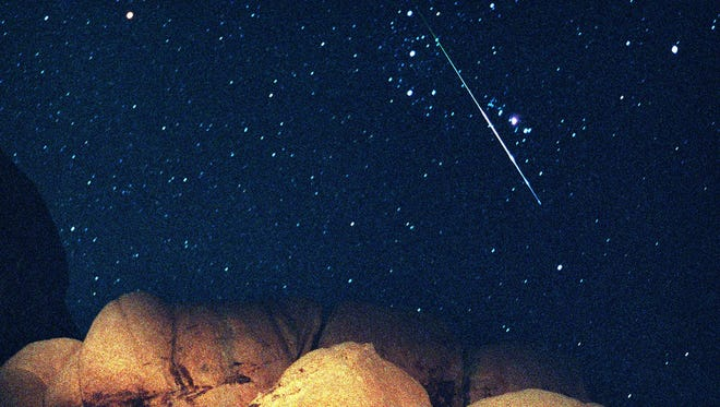 A bright Perseid meteor cuts across Orion's Belt during the peak of the annual Perseid meteor shower Aug. 12, 1997.