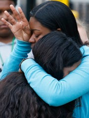 Howard students Diamond Brown (top) and Alexia Zurita embrace during a gathering of mourners Friday following the beating death of Amy Inita Joyner-Francis at Howard High School of Technology Thursday.