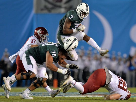 Michigan State's LJ Scott knocks the helmet off teammate Tyler Higby on his way to 110 yards rushing on 18 carries in the Holiday Bowl on Dec. 28 in San Diego.