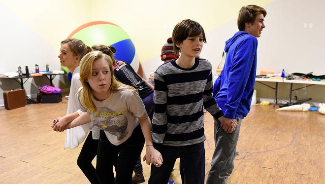 """James, played by Joseph Richards, center, and the insects ride in a giant peach during rehearsal of """"James & the Giant Peach"""" on Wednesday, Jan. 25, at GREAT Theatre in Waite Park."""