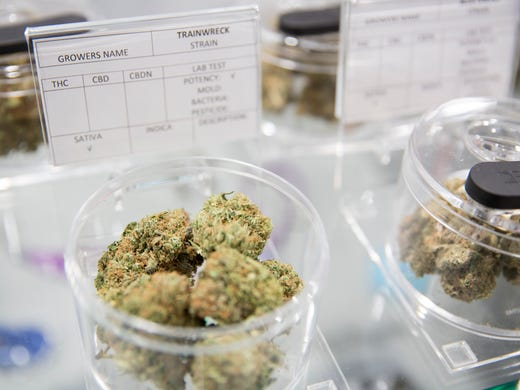 Varieties of marijuana on display in plastic canisters