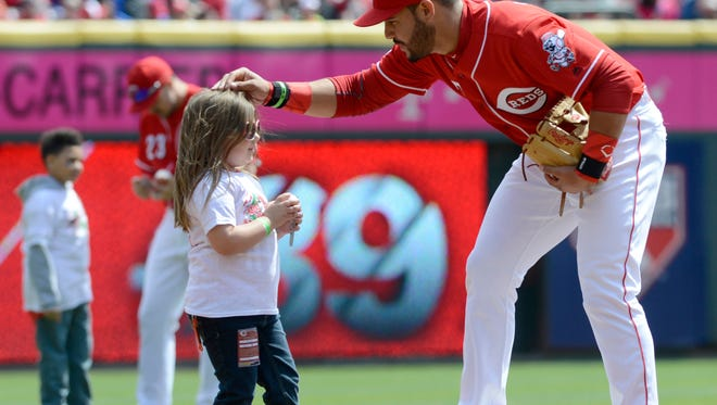 Cincinnati Reds third baseman Eugenio Suarez (right) talks with a fan on third base at the beginning of a game with the Pittsburgh Pirates at Great American Ball Park on Sunday.