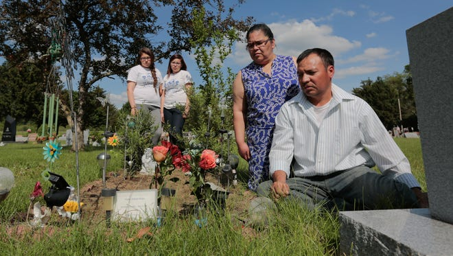 Jose and Leticia Perez sit at their son Victor Perez's grave at Mt. Hope Cemetery in Middleville, Mich., with daughters Jessica and Lorena Perez. Victor Perez was one of two teenage farmhands who suffocated cleaning a tank at Yankee Spring Dairy in Middleville in 2010.