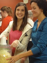 Trista Boudreaux and Christy Dickerson bag cornbread before one of Oak Grove UMC's annual Thanksgiving Dinners.
