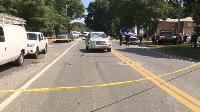 Police tape surrounds a car on Bishop Street in Framingham on Sunday where a 17-year-old bicyclist was struck and seriously injured.
