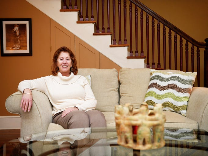 Lori Postal sits in the living room of her home November