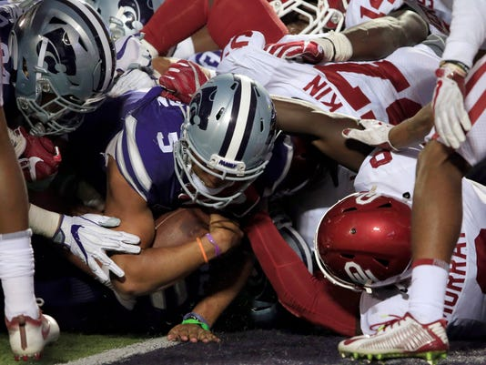 Kansas State quarterback Alex Delton (5) scores a touchdown against Oklahoma linebacker Kenneth Murray, right, during the second half of an NCAA college football game in Manhattan, Kan., Saturday, Oct. 21, 2017. Oklahoma defeated Kansas State 42-35. (AP Photo/Orlin Wagner)