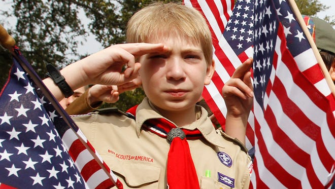 """Joshua Kusterer, 12, of Boy Scout Troop 226 in Plano, TX salutes during the """"Save Our Scouts"""" Prayer Vigil and Rally in front of the Boy Scouts of America National Headquarters in Irving, Texas , Feb. 6, 2013."""