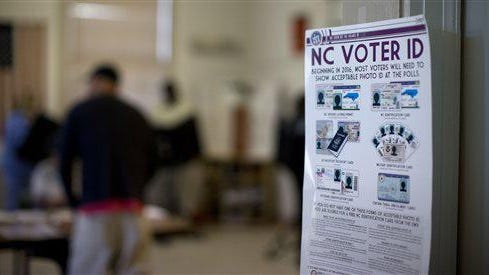NC Voter ID rules are posted at the door of the voting station at the Alamance Fire Station, Tuesday, March 15, 2016, in Greensboro, N.C. The voter ID law was later overturned in a lawsuit.