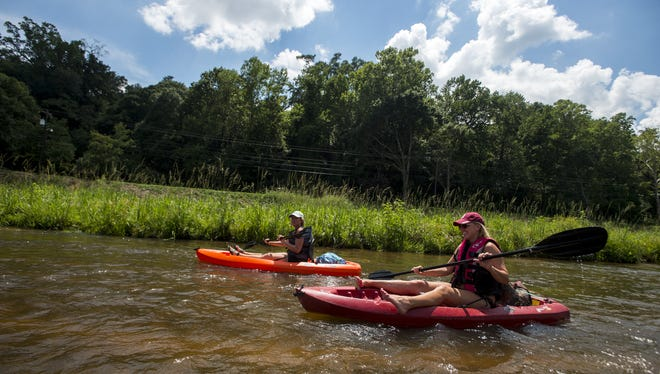 Patricia Healy Davis, left, and Tracey Burton kayak down the Autauga Creek Canoe Trail.