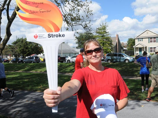 Kelly Long of Lebanon carring a torch in Honor of her Father John Fernsler of Lebanon who is a stroke suvivor, in the American Heart Association walk. FILE PHOTO