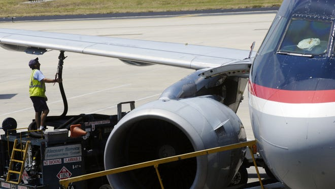 A worker hooks up a fuel hose to an airplane at Tampa International Airport.