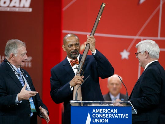 Milwaukee County Sheriff David A. Clarke Jr., center, holds up a rifle that was presented to him as part of his Charlton Heston Courage Under Fire Award at the Conservative Political Action Conference in February 2015 in National Harbor, Md.