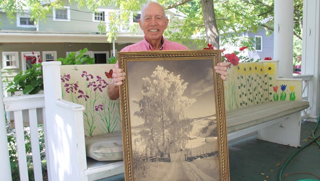 Bill Andrews, an emeritus professor at the College at Brockport, holds a photo from his collection of works by late Norwegian photographer Anders Beer Wilse.  Andrews recently donated the bulk of his collection to the National Library of Norway.