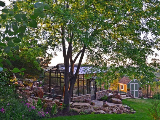 This greenhouse in Loveland is accompanied by a stone walkway, steps and water feature.