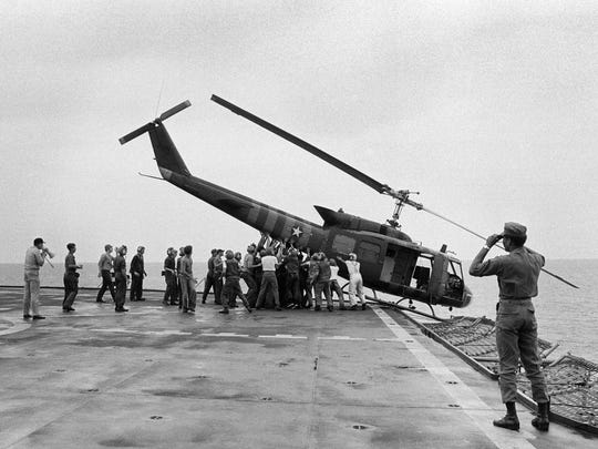 U.S. Navy personnel aboard the USS Blue Ridge push a helicopter into the sea off the coast of Vietnam in order to make room for more evacuation flights from Saigon on April 29, 1975. The helicopter had carried Vietnamese fleeing Saigon as North Vietnamese forces closed in on the capital.