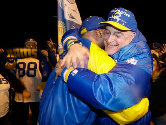Football fans hug after the announcement of the return of the Rams to Los Angeles on the site of the old Hollywood Park racetrack in Inglewood, Calif., Tuesday, Jan. 12, 2016. NFL owners voted Tuesday night, to allow the St. Louis Rams to move to a new stadium at the site just outside Los Angeles, and the San Diego Chargers will have an option to share the facility. The Rams, based in the LA area from 1946-94, will play in a temporary facility, probably the Los Angeles Coliseum, until the new stadium is ready for the 2019 season. (AP Photo/Damian Dovarganes)