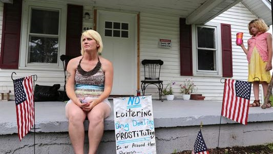 Tammy Breeding sits on her Austin, Ind., porch with her daughter. She made the yard sign to keep away drug dealers and prostitutes she said are still in the area, even as Scott County's HIV outbreak begins to ebb.