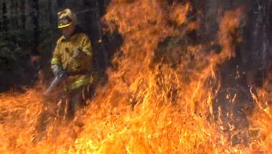 A state Forest Service firefighter lights a backfire near a brush fire in Barnegat in 2012.