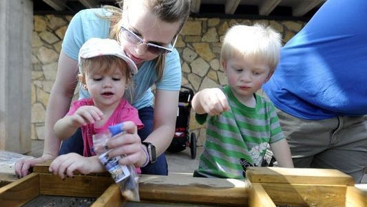 Penny Cooper, left, helps her daughter, Elsa, pan for fossils during the Abilene Zoo's Zoolute to Dyess on May 21, 2016. Cousin Adam Ackerman is also helping.