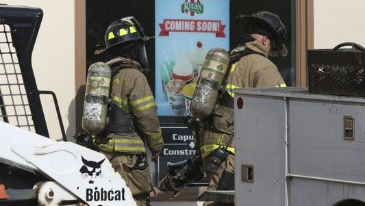 Emergency personnel work at a Rita's Water Ice under construction in Greenville's Powder Mill Square in Delaware after three people were sickened by carbon monoxide about 8:45 a.m Saturday, according to preliminary reports.