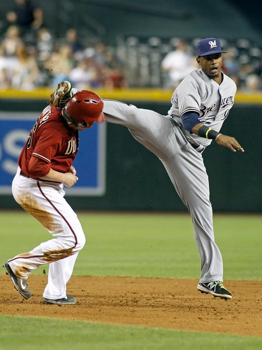 Milwaukee Brewers' Jean Segura, right, accidentally kicks Arizona Diamondbacks' Miguel Montero in the head while trying to leap over Montero on an inning ending double play during the sixth inning of a baseball game on Wednesday, June 18, 2014, in Phoenix. (AP Photo/Ralph Freso)