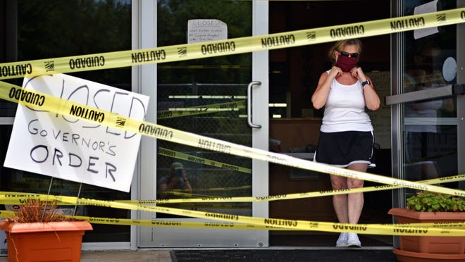 Linda Rogers exits the closed Randolph Tennis Center. Rogers is helping her daughter, Jennifer Rogers, owner of Randolph Tennis Center hang banners from local businesses along the fences of two outdoor courts Rogers recently installed to keep her business afloat during the coronavirus pandemic.