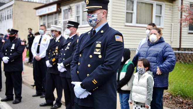 Members of the Oakland fire department attend a service for Gary Walker, 53, a longtime Bloomingdale police officer and firefighter for Oakland, outside of Bloomingdale Borough Hall on April 29, 2020. Walker died due to complications from Covid-19.