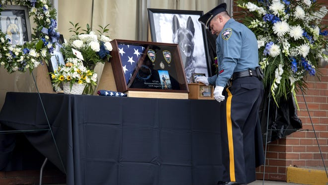 A memorial service was held outside the Hackettstown Police Department for K-9 Jada on August 31, 2020. K-9 Jada was working on August 19, 2020 when she suffered a medical emergency. Jada was rushed to a veterinary clinic where she died in the company of her handler Hackettstown Officer Christopher Laver. Officer Laver rests his hands on a box containing Jada's ashes as he is the last one to say good-bye to her.