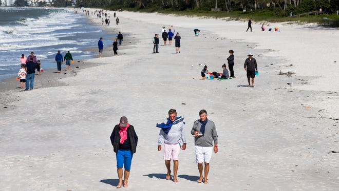 People wear scarves and jackets as they walk along the beach near the Naples Pier on Tuesday, Jan. 2, 2018. The strong north wind caused temperatures to drop into the low 60s.