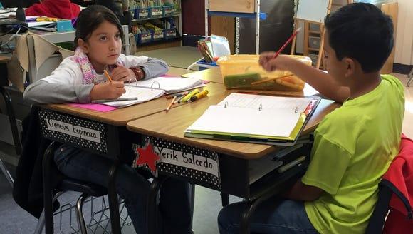 Students in a third-grade class do a math assignment