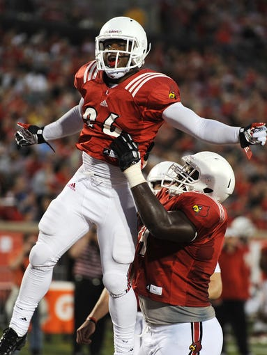 Louisville's Michael Dyer (left) is hoisted by teammate DeAngelo Brown after Dyer scores a touchdown against the white team against on Friday during the 2014 UofL Football Spring game at Papa John's Cardinal Stadium. April 11, 2014