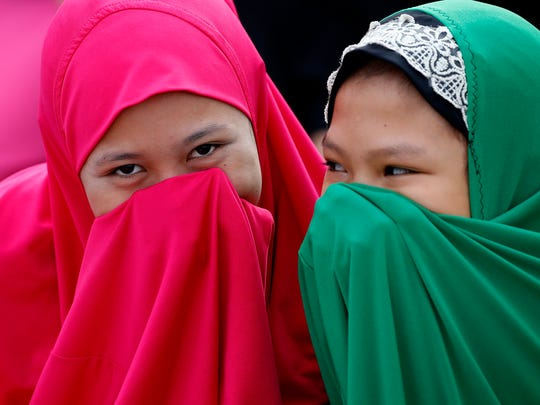 Filipino Muslims cover their faces as they gather outside the Blue Mosque to pray in celebration of Eid al-Fitr Friday, June 15, 2018 at the Blue Mosque in suburban Taguig city, east of Manila, Philippines. Muslims all over the world mark Eid al-Fitr with prayers, family reunions and gift-givings. (AP Photo/Bullit Marquez)