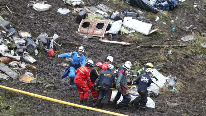 Rescue workers recover a body from the wreckage site of an airplane crash, in La Union, a mountainous area near Medellin, Colombia, on Nov. 29, 2016.