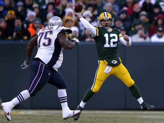 Green Bay Packers' Aaron Rodgers throws under the pass rush of New England Patriots' Vince Wilfork.  The Green Bay Packers host the New England Patriots Sunday, November 30, 2014, at Lambeau Field in Green Bay, Wis.  Wm.Glasheen/P-C Media