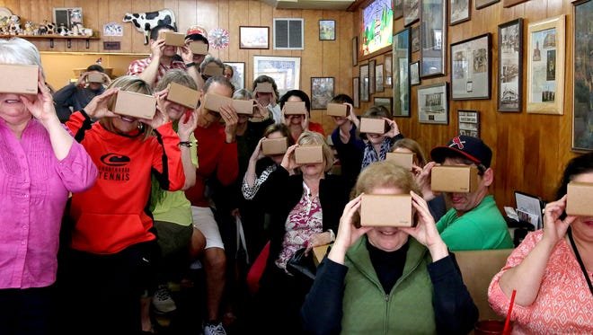Court Street Dairy Lunch patrons hold Google Cardboard virtual reality viewers, which will be given out to dinner guests a SEDCOR dinner next month.