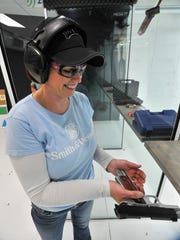 Trudy Lotter, of Wausau, loads her pistol magazine during a shooting Friday afternoon at Zingers & Flingers indoor shooting range in Wausau.