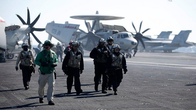 U.S. Navy crew members walk on the deck of the USS Ronald Reagan, a Nimitz-class nuclear-powered super carrier, during a drill Wednesday in South Korea