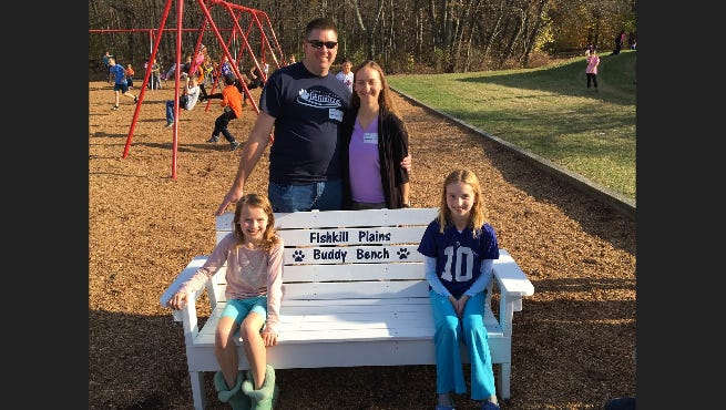 Tom Curtiss, his wife, Suzanne and daughters Ashley, left and Daniella, right, pose with the Buddy Bench they donated to the Fishkill Plains Elementary School.