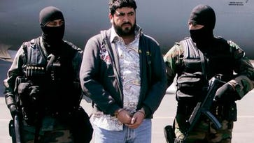 """In this Jan. 21, 2008, photo, Mexican federal police officers escort Alfredo Beltran Leyva, known as """"El Mochomo,"""" after his arrest upon his arrival at Mexico City's airport. """"El mochomo"""" is a big, biting ant in northwestern Mexico."""