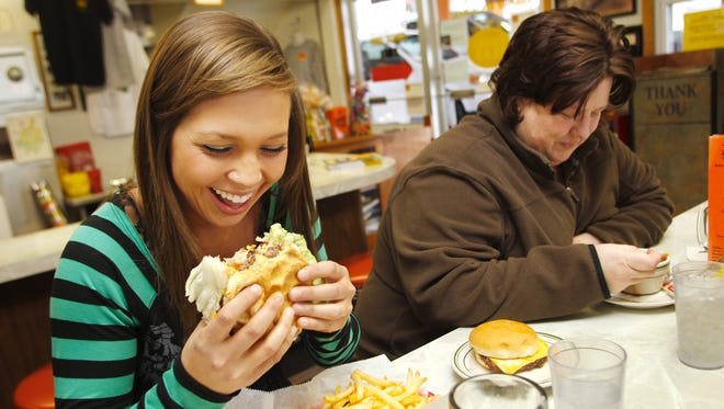 Ashely Velez, left, enjoys a Duane Purvis All-American burger as she enjoy lunch with her mother Robin Catlin Friday, January 20, 2012, at Triple XXX Family Restaurant, 2 N. Salisbury Street in West Lafayette.