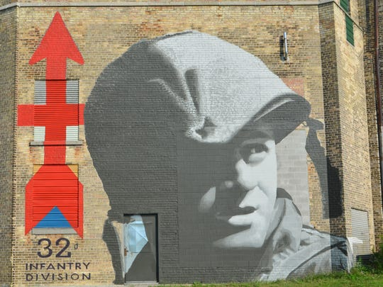 The mural, on the side of the Historic Richter Vinegar Plant, was inspired by a black-and-white photo of a 32nd Infantry Division (Red Arrow Brigade) soldier, D.F. Hirsch of Milwaukee, a Specialist Fourth Class. His image was taken by a military photographer during training at Fort Lewis in Washington state in May 1962, preparing for a potential threat in Berlin.